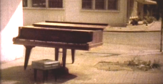 A still from footage taken in Phnom Penh after its fall in April 1975. A grand piano also features in Dalrymple's Monrovia Mon Amour, in the chapter describing a visit to the Centennial Hall. Dalrymple writes: 'Lying on the ground…was a Steinway grand piano (the only one in the country…), its legs sawn off. The body of the piano, still gleaming black and in perfect condition, was in direct contact with the floor, while the three sawn legs were strewn about….A long-contemplated but long-frustrated revenge upon a whole alien civilization…. simmering rage and envy….Michel took photos of the stricken instrument….How long…before some post-modernist composer has a pianist not play the instrument but, in front of the audience, saw off its legs, to the craven applause of critics afraid to be thought stupid or reactionary?….We felt we had secured something of a scoop….We returned to the Olympic Hotel….There we found two…British photographers….I described to them…the destruction of the piano….'What do we care about a fucking piano?' one of them said….I despaired then of my own country.'